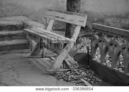 Old Wooden Bench With Peeling Paint Near Stone Fence, Bw Photo.