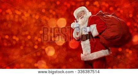 Good old Santa Claus with a bag of gifts shakes his finger under a snowfall on a red shimmering background. Merry Christmas and Happy New Year! Copy space.