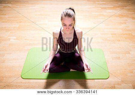 Athlete Meditates On A Sports Mat. Lighting From The Back