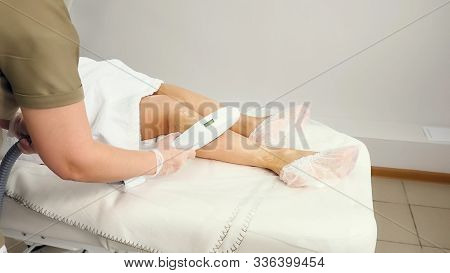 Woman Hands Do Laser Epilation Treatment On Leg Side Part To Girl Lying In Robe On Table In Medical