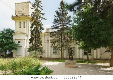 Yevpatoria, Crimea, Russia-september 07, 2019: Sculpture Of A Boy With A Weight Near The Old Buildin