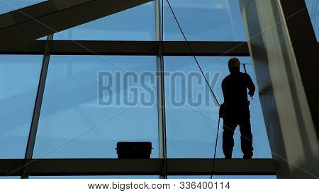 Worker Man Is Washing Windows With Scraper On A Highrise Modern Building Hanging The Rope, Close-up