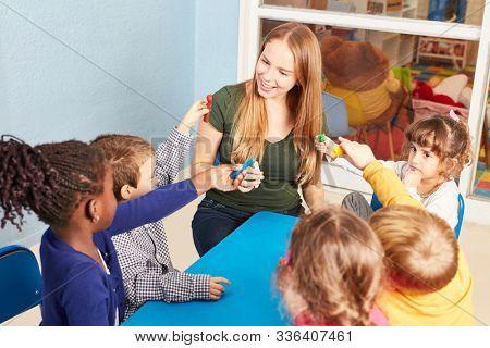 Kindergarten teacher and group of children with play dough in a craft workshop in kindergarten