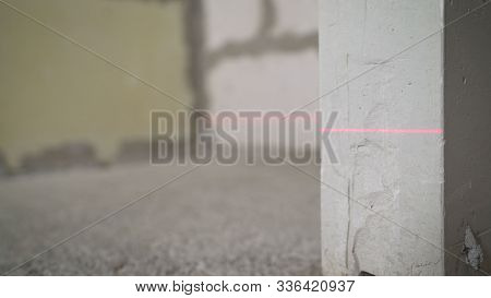 Leveling The Wall With A Laser Level. Lighted Laser Level. Display Perpendicular Lines. Laser On The