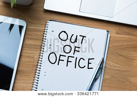 Out Of Office Message On Notepad With Pen Near Laptop And Digital Tablet