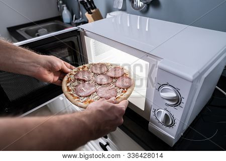 Human Hand Baking Pizza In Microwave Oven