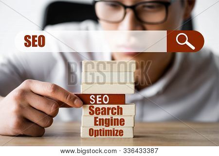Selective Focus Of Asian Seo Manager Holding Wooden Rectangle With Lettering Seo And Sitting Near Se