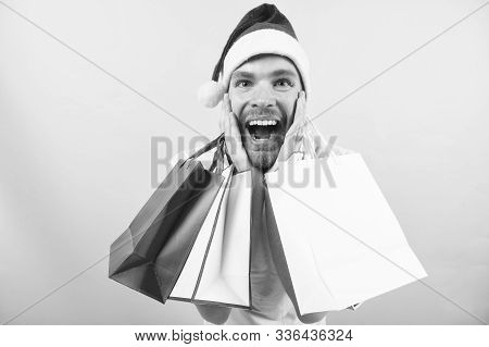 Christmas, New Year Surprise, Presents. Man In Santa Hat With Bags On Orange Background. Winter Sale