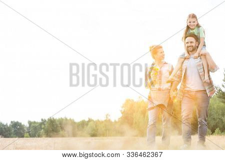 Happy family walking in wheat field with yellow lens flare