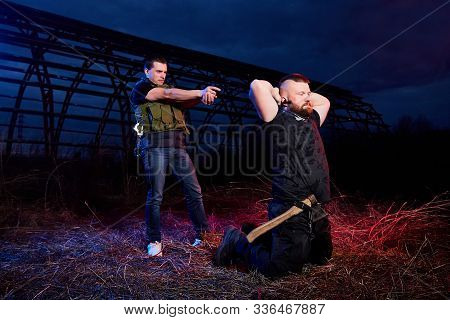 Soldier And Instructor At Night Outdoors. A Short Man Paratrooper And A Large Brutal Male Instructor