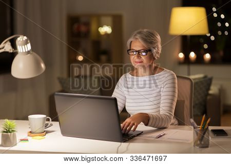 technology, old age and people concept - senior woman in glasses with laptop working at home in evening