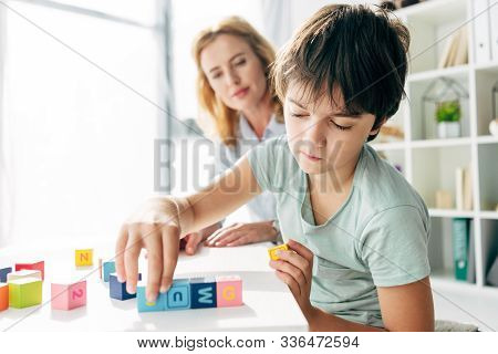 Selective Focus Of Kid With Dyslexia Playing With Building Blocks And Child Psychologist Looking At