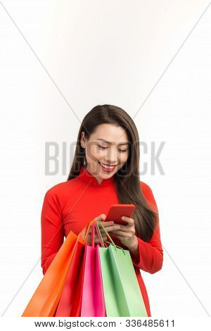 Woman In Ao Dai Using Smartphone And Holding Shopping Bag On White Background