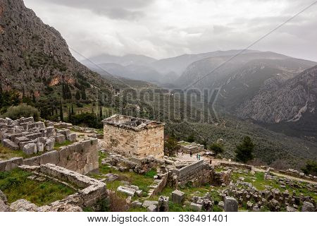 The Landscape Of Ancient Delphi In Greece With Treasury Of Athenians And Cloudy Weather In The Backg