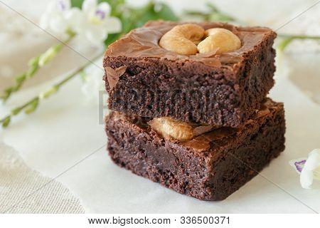 Fresh Baked Dark Chocolate Fudge Brownies. Sweet Brownie Topping With Cashew Nut Stacked On White Pa