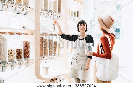 Shop Assistant Helping Customer In Bulk Food Store.