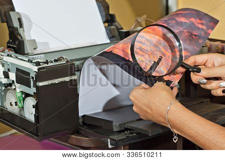 The Girl In A White Shirt Prints A Photo. Woman Looking Through Photo With Magnifier. The Glasses As