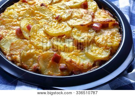Close-up Of A Delicious, Cheesy, Gooey Casserole Of Potatoes With Smoked Ham In A Baking Dish, Horiz
