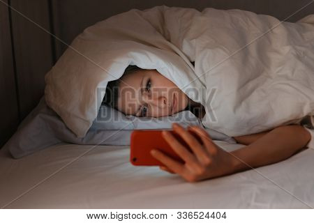 Young Woman Can't Sleep And Using Her Smartphone In Beg At Night.