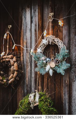 Christmas Wreath On Rustic Wooden Door Background Of Blue Tree. Christmas New Year Background For Gr