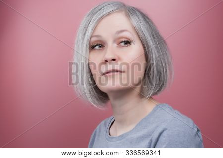 Beautiful Woman In Her Early Fifties Wearing Fake Lashes, Pink Background