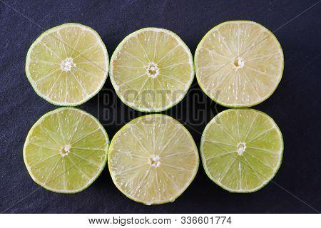 Six Juicy Lime Halves On A Black Slate Background