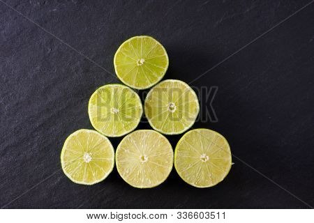 A Pyramid Of Lime Halves On Black Slate Ready For Use In Food Or Cocktails