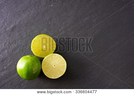 Two Halves Of A Lime Next To A Whole Lime On A Black Slate Background With Copy Space