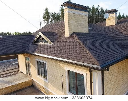 House With A Roof From A Bituminous Tile. New Brick House. Bituminous Tile For A Roof. A Roof From A