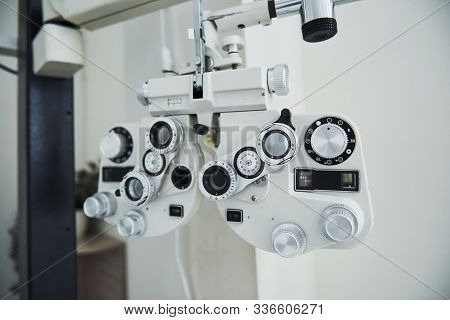 Phoropter Standing In The Office. Ophthalmologist Devices In The Beautiful White Room.