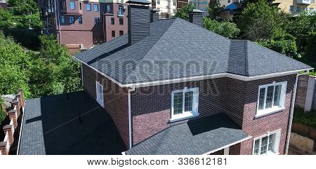 House With A Roof From A Bituminous Tile. Bituminous Tile For A Roof. A Roof From A Bituminous Tile.