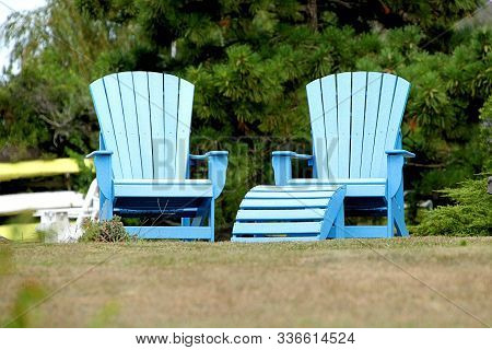 Pair Of Blue Adirondack Chairs Sitting In A Backyard On A Sunny Summer Day.