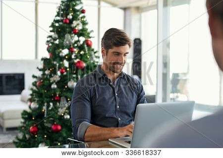 Happy young businessman working on laptop during christmas holiday. Successful business man in modern office working with xmas tree in background. Entrepreneur using laptop in modern office.