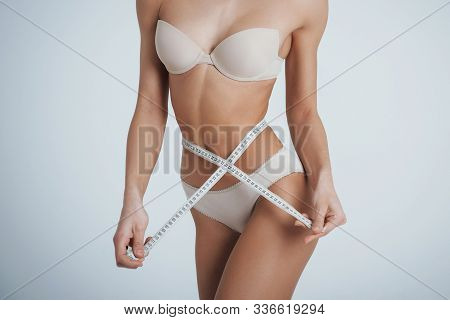 Girl In The White Underwear With Centimeter Tape Around Her Waistline.