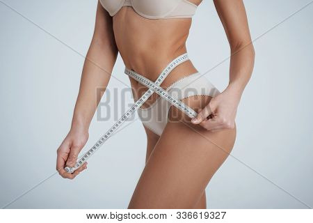 The Results Of Sports. Girl In The White Underwear With Centimeter Tape Around Her Waistline.