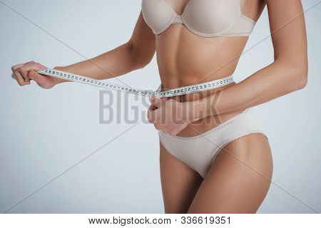 Circumference Measurement. Girl In The White Underwear With Centimeter Tape Around Her Waistline.