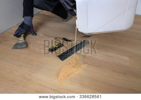 Master Parquet With Glue Bin In Your Hand. Preparation Of Parquet Grout Material. Mixing Retainer, V