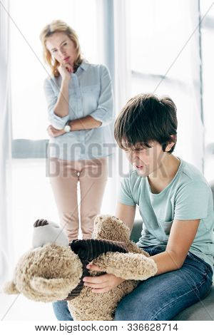 Sad Kid With Dyslexia Holding Teddy Bear And Child Psychologist Looking At Him