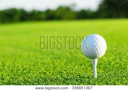Golf Ball On Tee On Golf Course Over A Blurred Green Field At The Sunset. Golf Ball On Tee Over A Bl