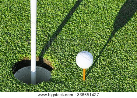 Golf Hole With Flag On Green Grass Of Golf Course. View Of Golf Hole On Green Field. Playing Golf. G
