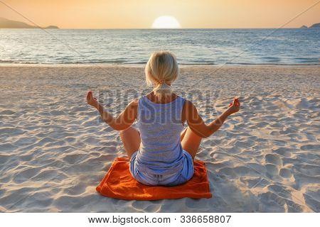 Woman Practicing Yoga On Sea Beach During Sunset. Beautiful Yoga Background.