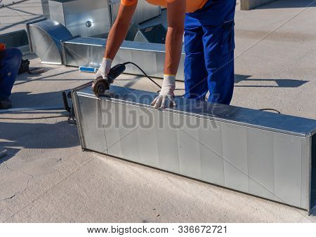 Hvac Technician Is Working On A Roof Of New Industrial Building. Close-up View Of The Young Technici