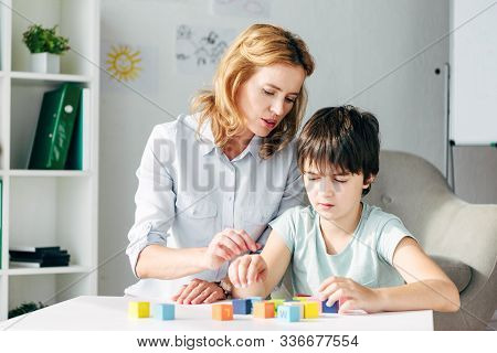 Child Psychologist And Kid With Dyslexia Playing With Building Blocks