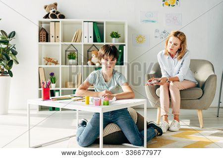Kid With Dyslexia Looking At Camera And Child Psychologist Looking At Him