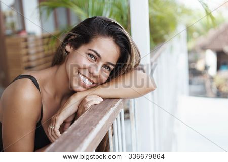 Happiness, Women And Tourism Concept. Cheerful Good-looking Young Tanned Woman Lean On Terrace Rail