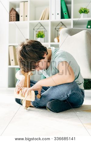 Kid With Dyslexia Sitting On Floor And Holding Wooden Plane
