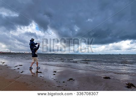 Aberdeen, United Kingdom - August 17, 2014: Father And Son On The Beach Look At The Stormy Sky. Aber