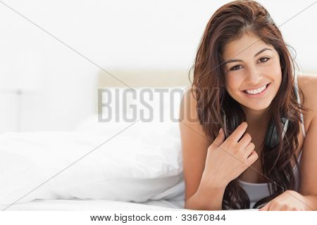 A woman at the end of the bed smiling and holding part of the hair in her hand while she looks straight ahead.