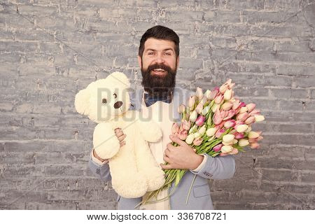 Romantic man. Macho getting ready romantic date. Waiting for darling. Man well groomed wear tuxedo bow tie hold flowers tulips bouquet and big teddy bear toy. Invite her dating. Romantic gift. poster