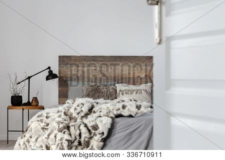 Open Door To Grey Elegant Bedroom Interior With Rustic Design, Copy Space On Empty Wall